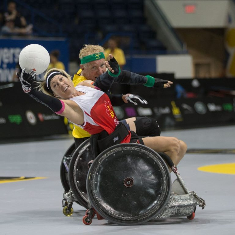 Hélène LeScelleur, seated in a wheelchair, reaches for a ball with one hand while a male competitor, also in a wheelchair, tries to take it from her.