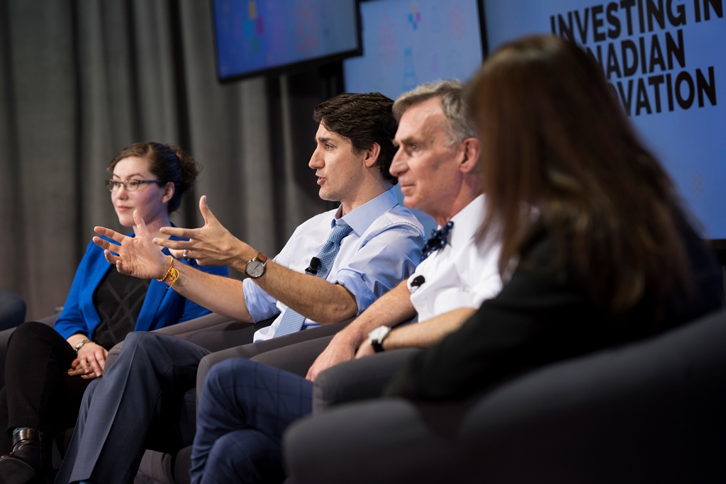 Prime Minister Justin Trudeau, sharing a stage with Bill Nye and two women, speaks to an unseen audience.