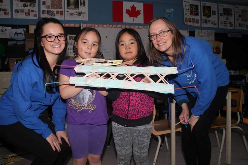 Two women pose with two girls holding a paper model of a bridge.