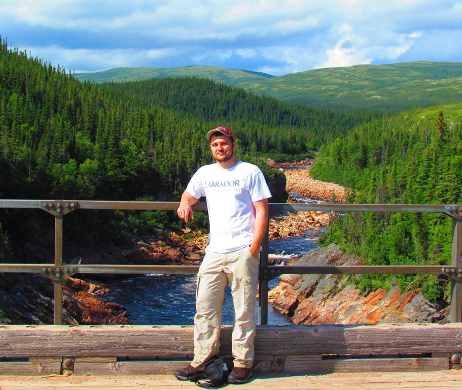 Robert Way leaning against a bridge railing above the winding Pinware River in Labrador.