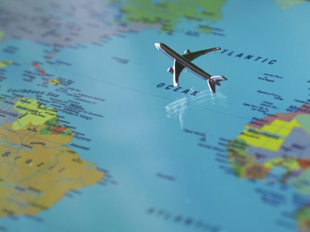 Montage d'un petit avion de métal qui survole une carte du monde plate.