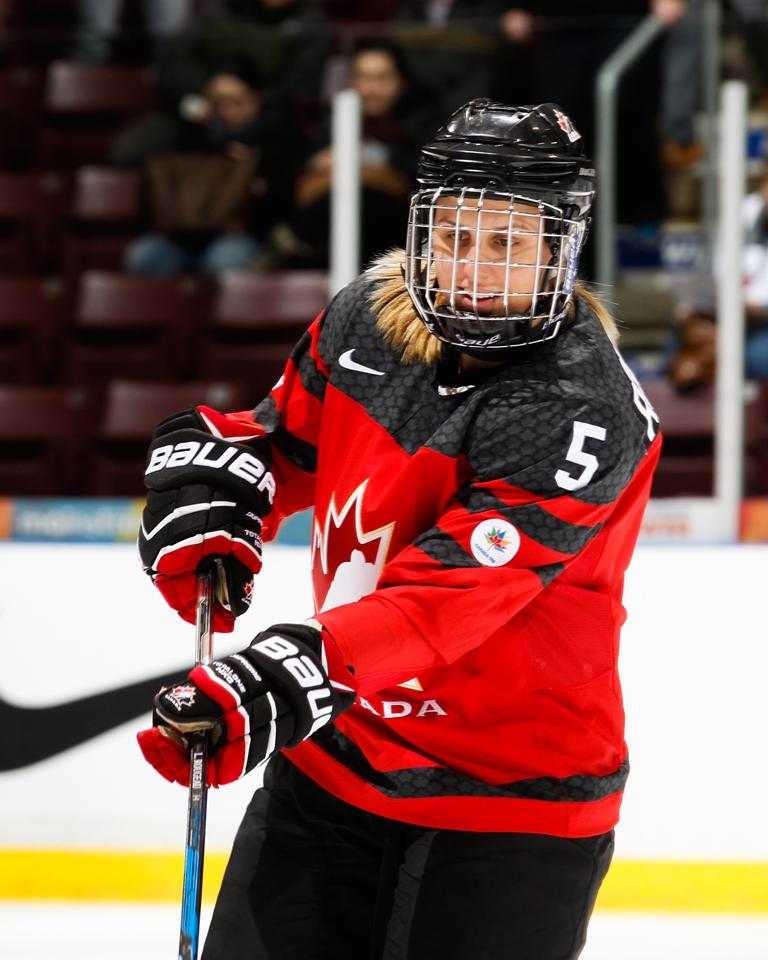 : Une joueuse de hockey, le visage derrière la grille de son casque et une crosse dans les mains, se concentre pendant un match.