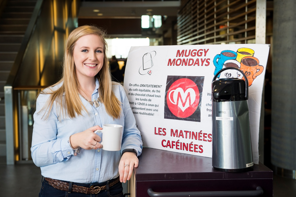 A smiling woman with long straight hair holds a mug while standing beside a poster advertising Muggy Mondays.