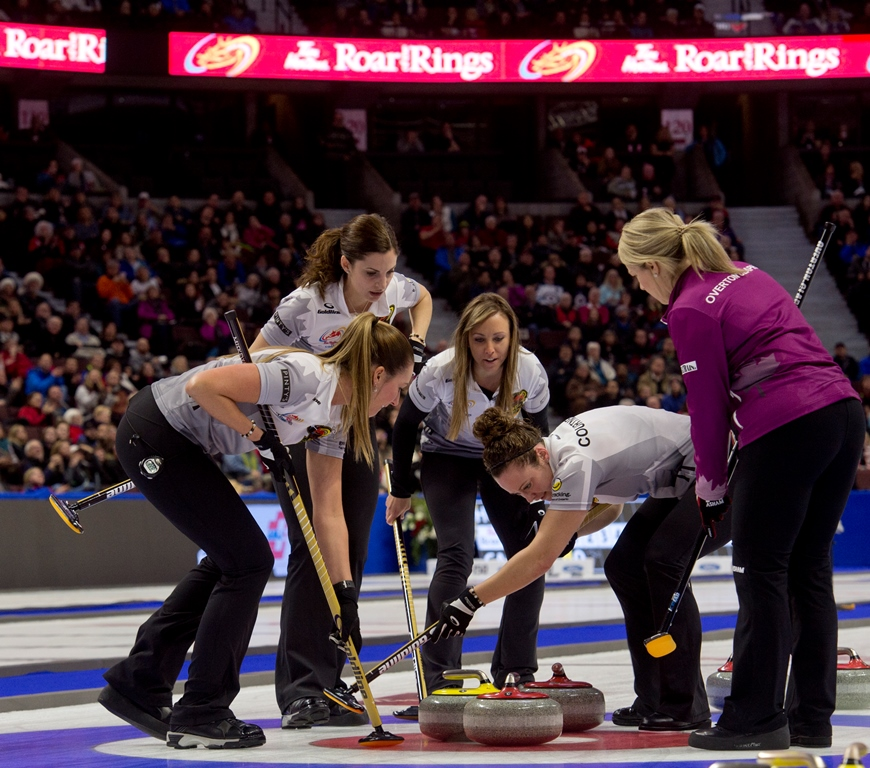 Five women compete in front of a large audience.
