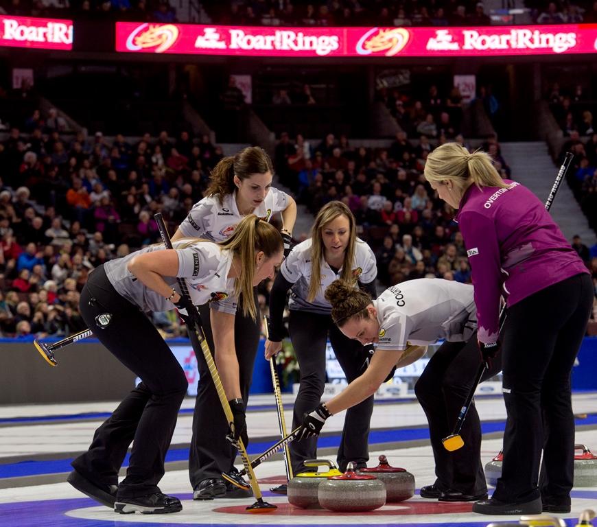 Cinq jeunes femmes disputent un match de curling devant une foule de spectateurs.