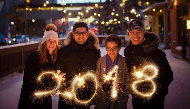 Four uOttawa students hold sparklers forming the shape of the number 2018