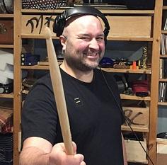 Rise Ashen sourit en tendant un bâton dans son studio regorgeant d'albums et d'instruments.