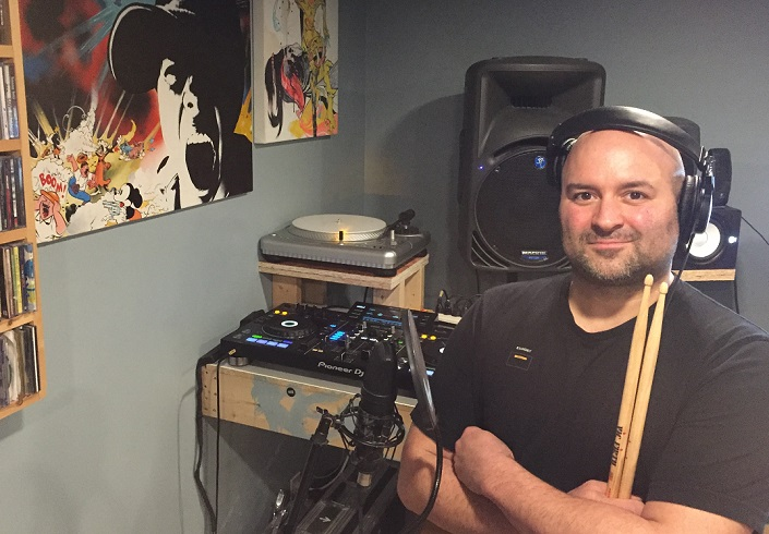 Rise Ashen in his basement recording studio with a turntable, speakers and other recording equipment behind him.