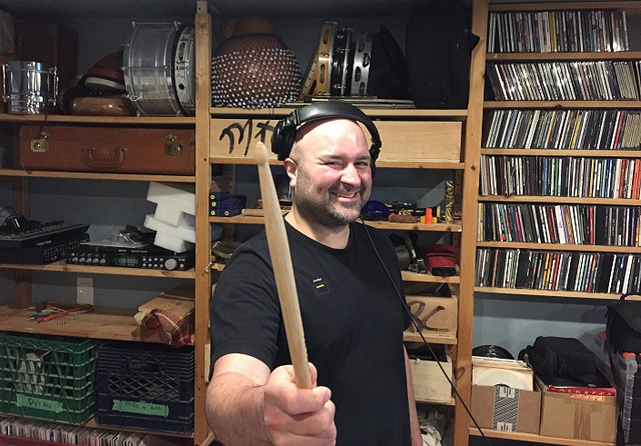 Rise Ashen stands smiling in his studio in front of shelves with many CDs and small musical instruments.