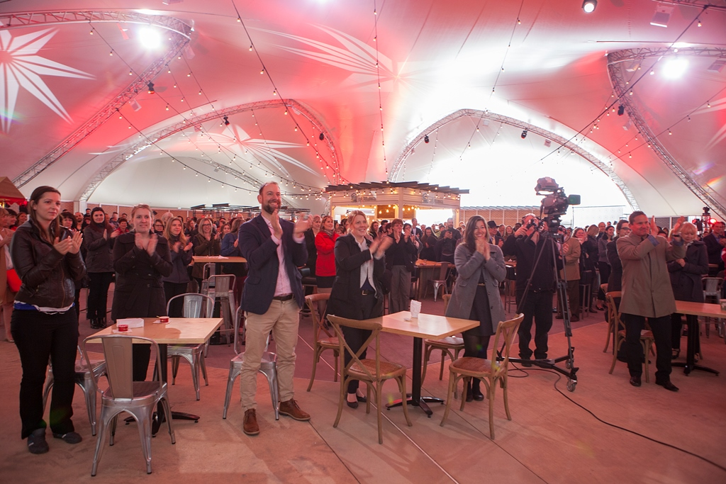 Employees applaud after Allan Rock's speech in the arabesque tent at University Square.