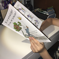 Un enfant tient le livre intitulé « Il se prenait pour le roi de la maison».