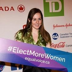 Roxanne Dumoulin, étudiante de l'Université d'Ottawa, est debout et tient une affiche sur laquelle on peut lire #Elect More Women.