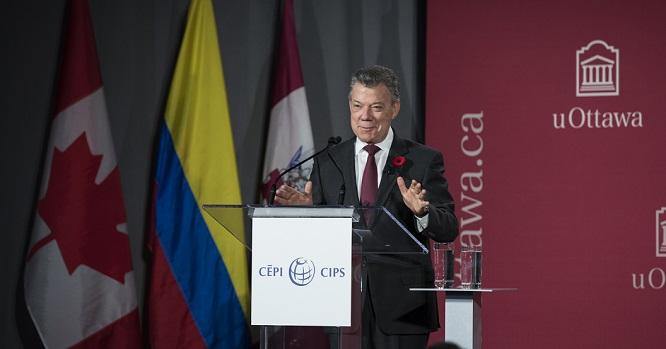 Juan Manuel Santos sur le podium, devant les drapeaux du Canada et de la Colombie, le logo de l'Université d'Ottawa en arrière-plan.