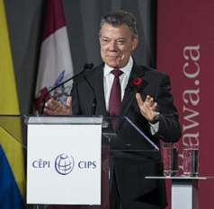 Juan Manuel Santos stands behind a lectern, with the uOttawa logo in the background.