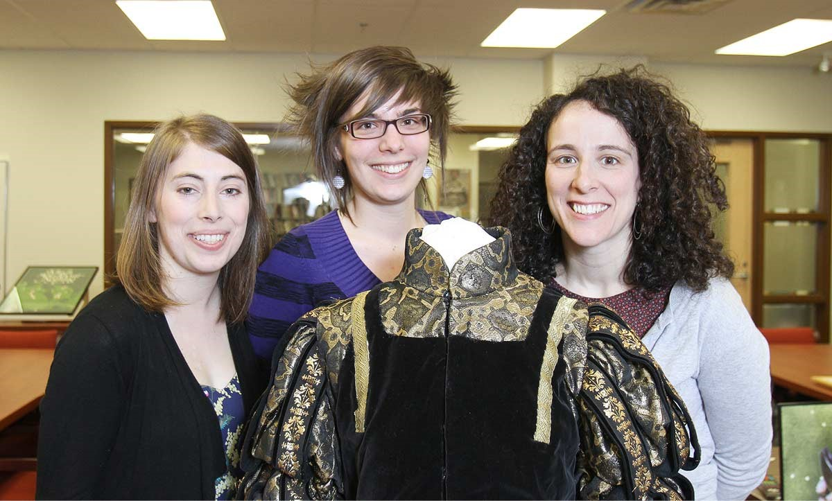 Three women stand behind a costume from the Shakespeare play Henry V.