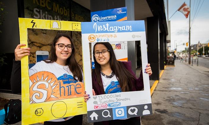Deux étudiantes posent derrière des cadres de carton.