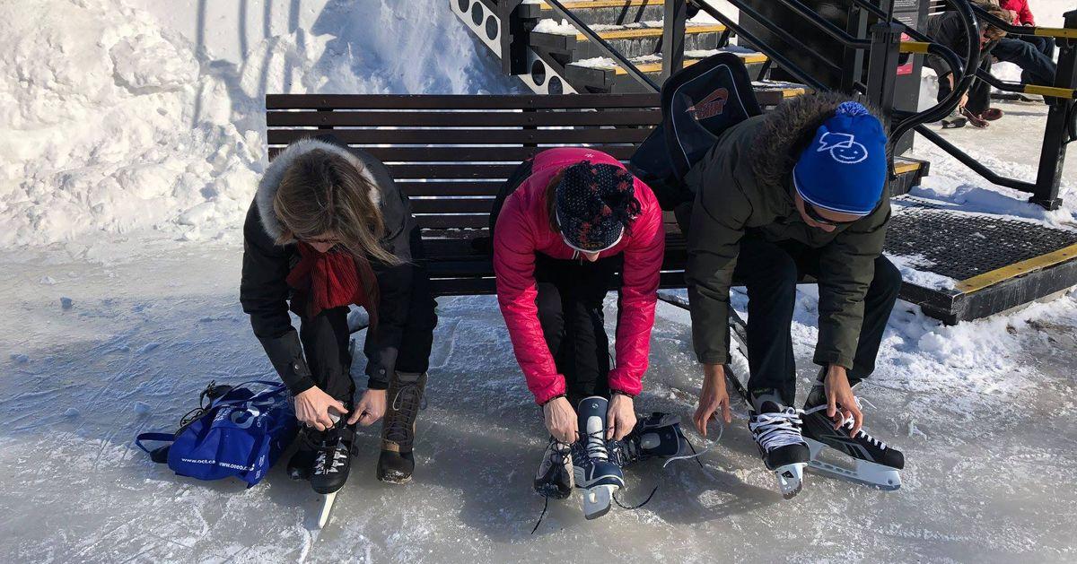 Trois patineurs assis sur un banc, attachent leurs patins.