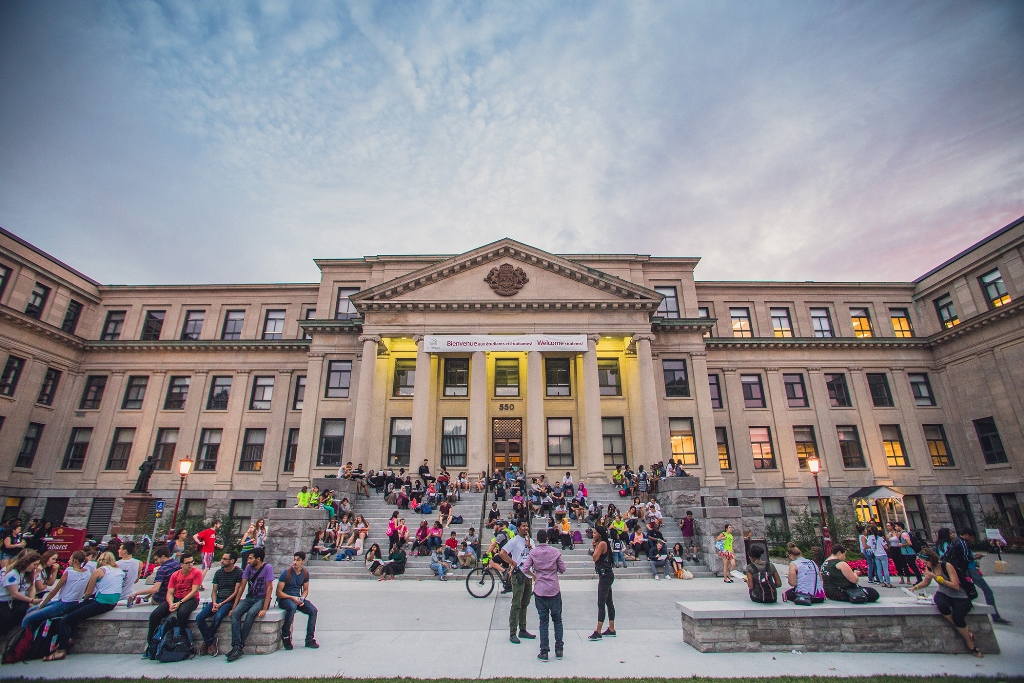 The front façade of the Tabaret building with students sitting around the courtyard and on the steps.
