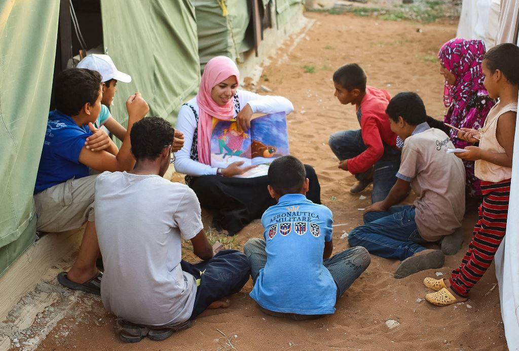 Woman reading a story to children in a refugee camp
