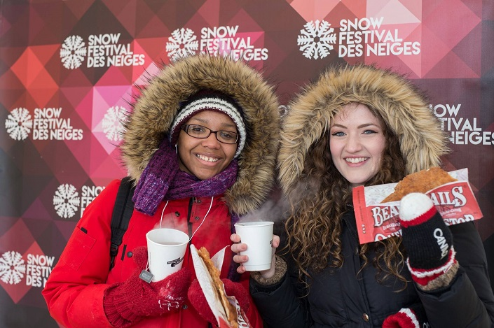 """Two young women (one wearing glasses) dressed in fur-lined parkas standing in front of a wall with the words """"Snow Festival des Neiges."""""""