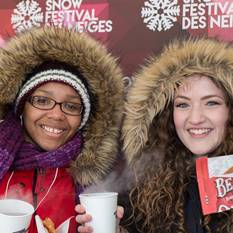 "Two young women (one wearing glasses) dressed in fur-lined parkas standing in front of a wall with the words ""Snow Festival des Neiges."""