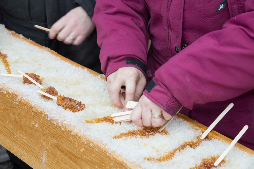 Rows of maple syrup taffy on a bed of snow with a pair of hands holding popsicle sticks