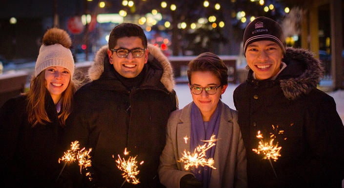Four students bundled in winter coats hold lit sparklers.