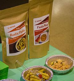 Sur un stand, deux emballages scellés de repas prêts à cuisiner, derrière un échantillon préparé de chacun.