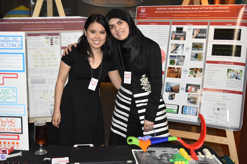 Two women, arm-in-arm, smile with posters in the background describing their VitalTracer device.