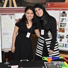 Deux femmes, bras dessus bras dessous, sourient devant des affiches décrivant leur appareil, le VitalTracer.