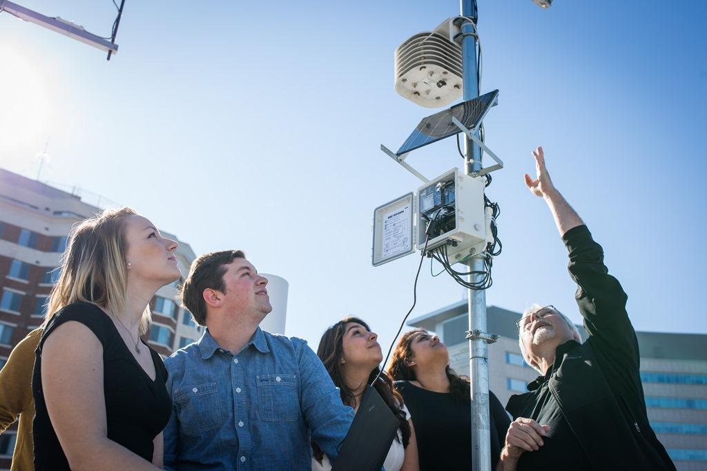 Quatre étudiants et un professeur autour d'une des stations météorologiques de l'Université d'Ottawa.