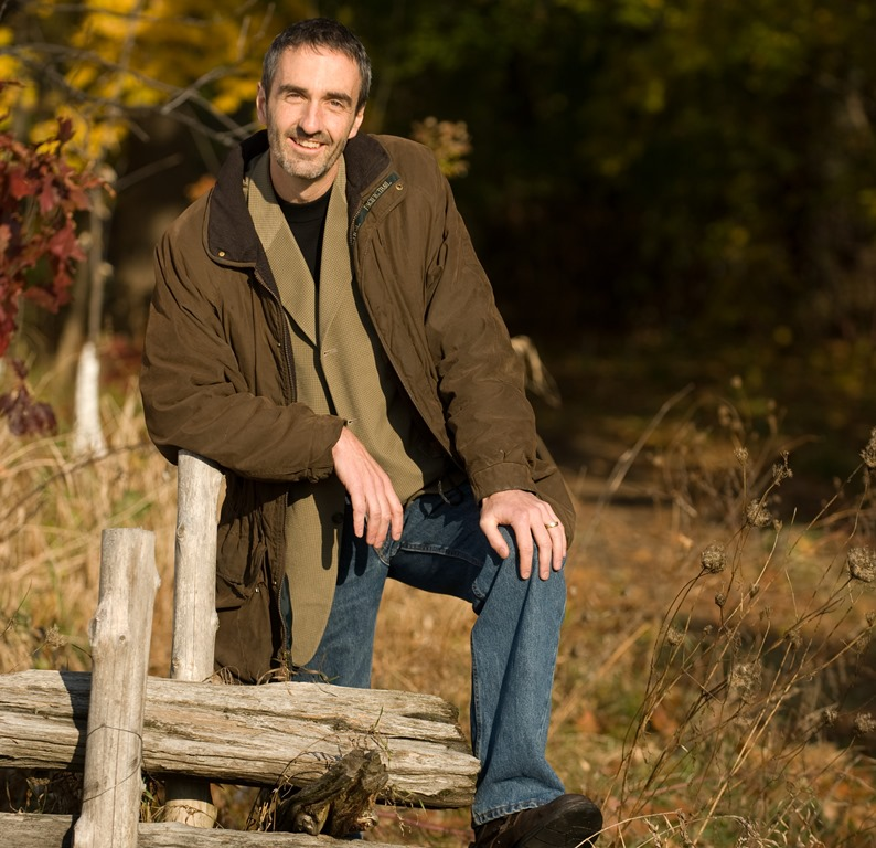 Stewart Elgie standing outdoors, near a wooded area.