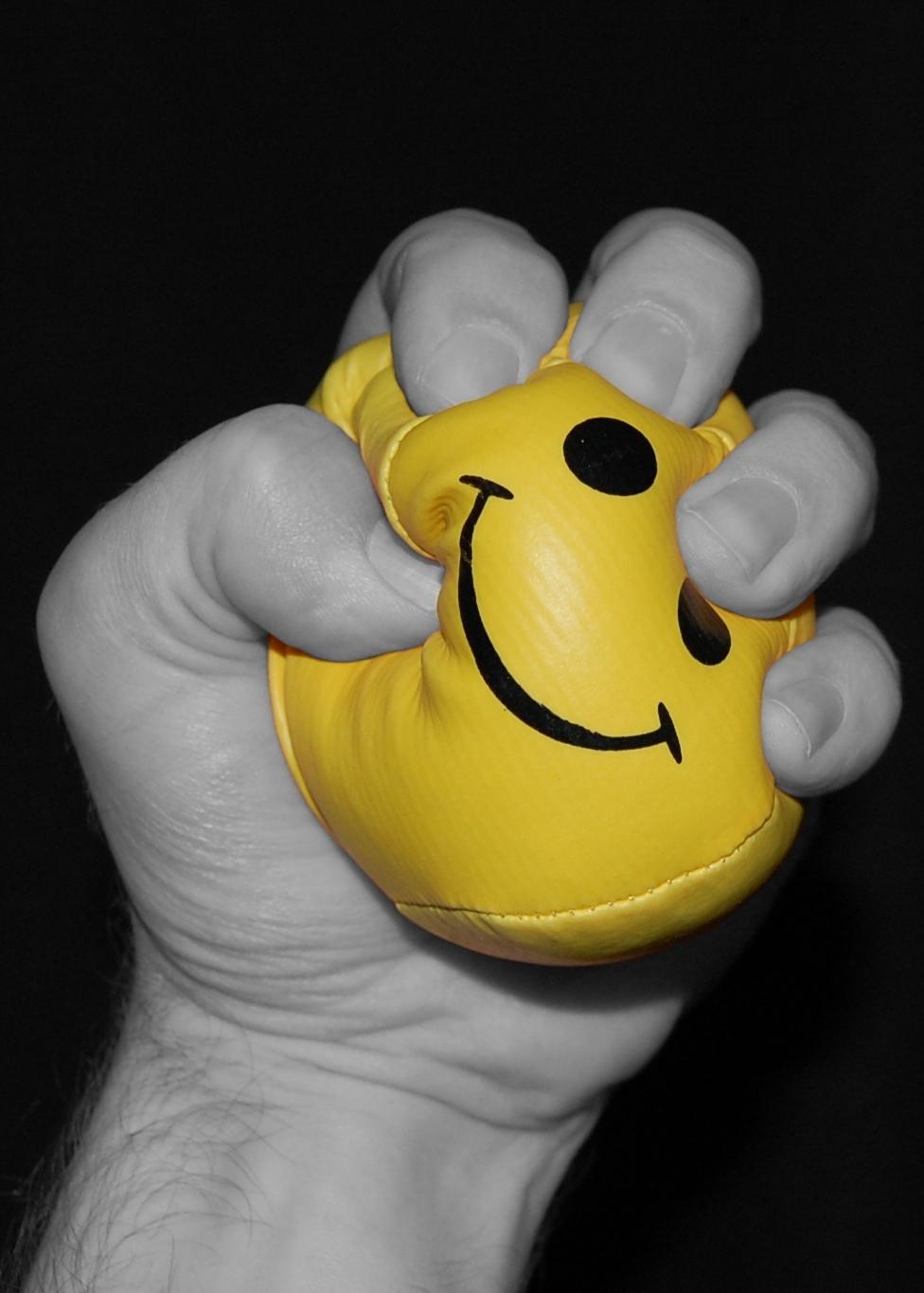 Une main serre une balle de stress.