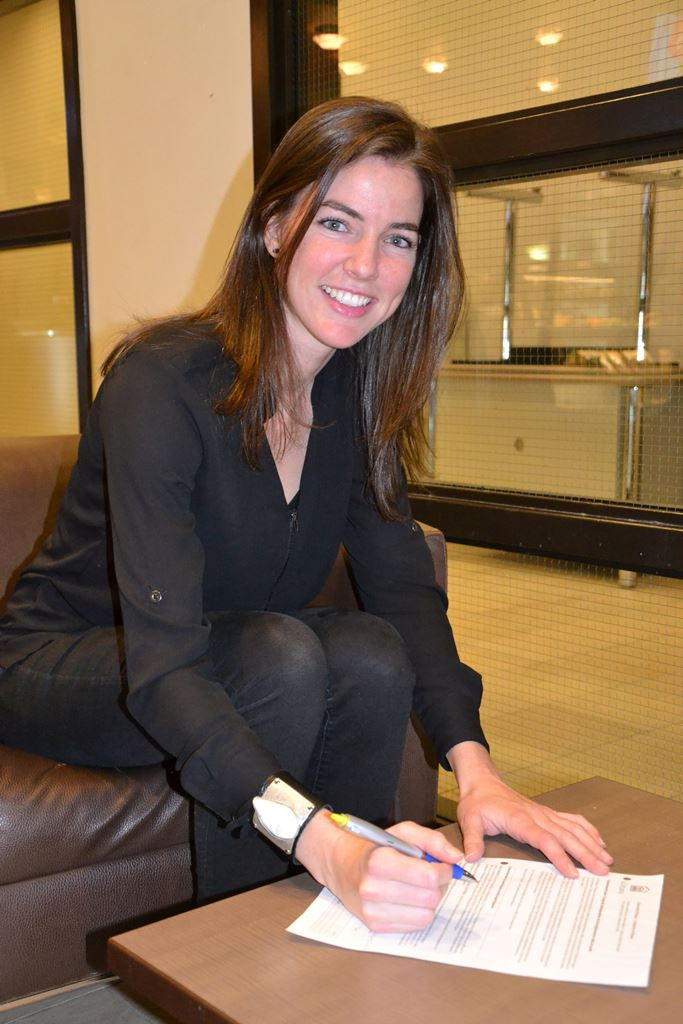 Marie-Pier Couture sits in an armchair with a pen in her hand and smiles at the camera.