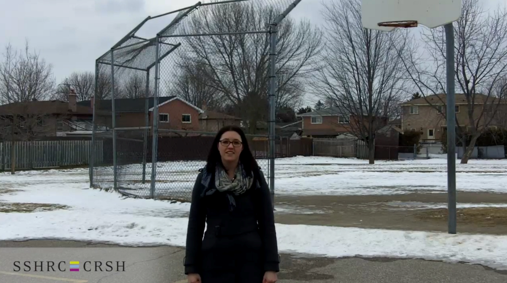 Karen Bouchard stands in a playground with a baseball backstop and basketball hoop in the background. Patches of snow are on the ground.