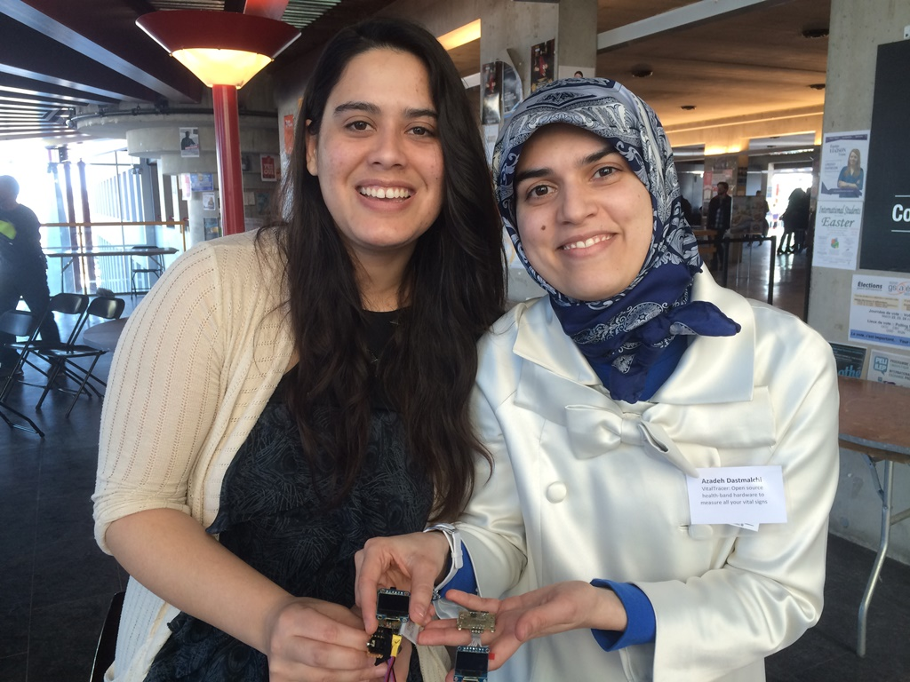 Two women, one wearing a head scarf, smile, holding the electronic components of a pulse oximeter.