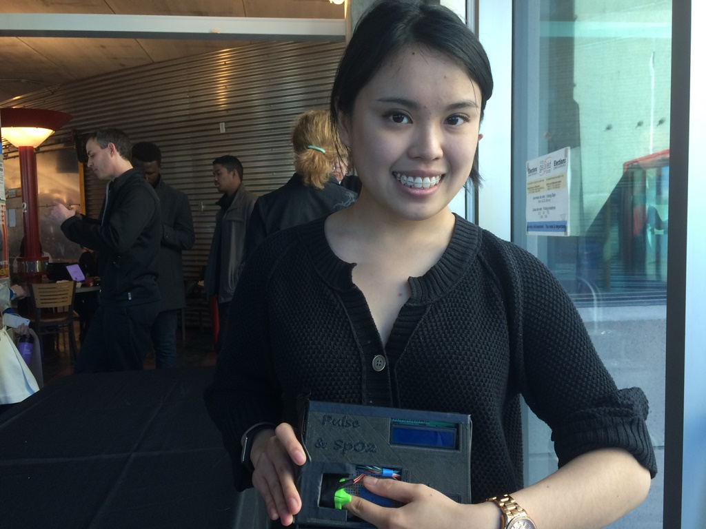 A woman smiles holding a plastic pulse oximeter.