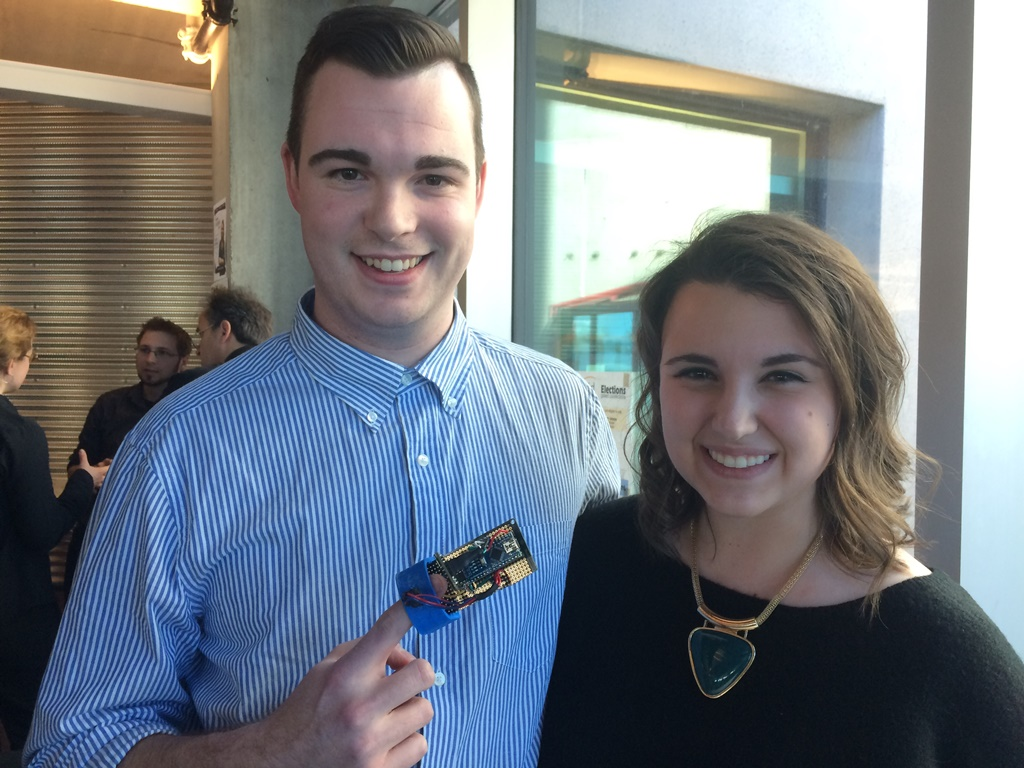 A man, with a finger in a pulse oximeter, stands next to a woman, smiling.