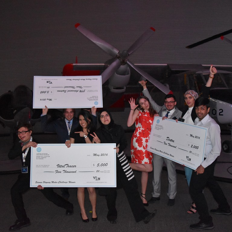 Group of eight students holding giant cheques and jubilantly celebrating, with a propeller aircraft in the background.