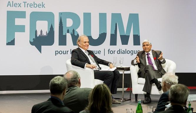 Deux hommes assis dans des fauteuils sur une scène. Le logo du Forum Alex-Trebek pour le dialogue est en toile de fond