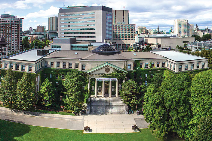 Aerial photo of the University of Ottawa's Tabaret Hall surrounded by leafy trees.