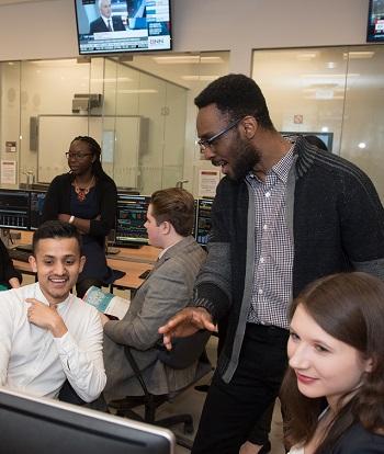 Plusieurs étudiants discutent ensemble dans une salle de classe avec des ordinateurs et des écrans de télévision