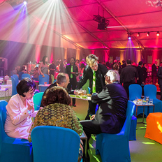 Alumni sit at a table eating and talking as other guests network and mingle under beams of colourful light at the Defy the Conventional Gala.