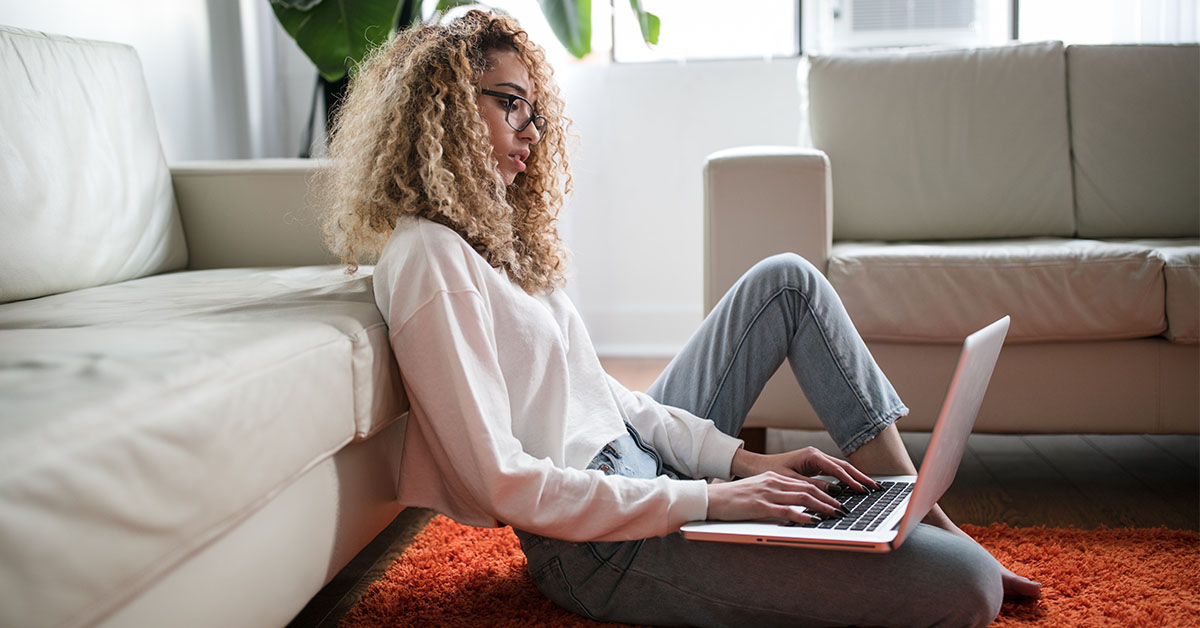 student sits on floor in living room typing on laptop computer