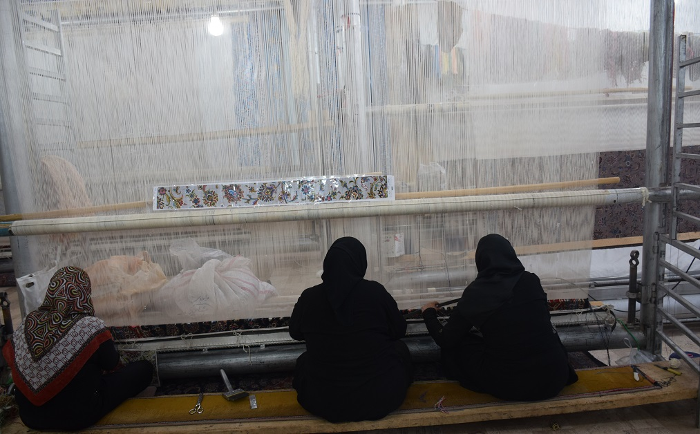 Three women weaving on a large carpet loom, shot from behind.
