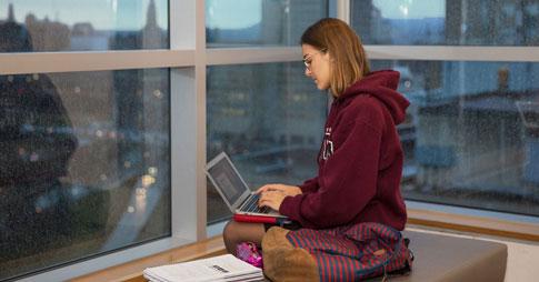 Une étudiante qui travaille avec son ordinateur portable
