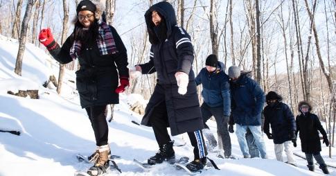 Un groupe d'étudiants font de la raquette sur neige dans le bois