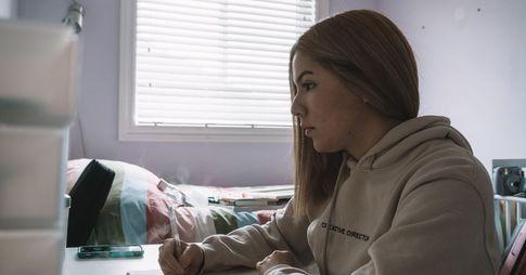 Une jeune femme vue de profil. Elle est assise à un bureau dans sa chambre à coucher.