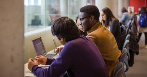 Groupe d'étudiants travaillant sur un ordinateur portable dans un espace commun.