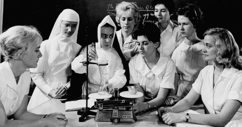 archival photo of a group of women in a chemistry class observing a chemical reaction.